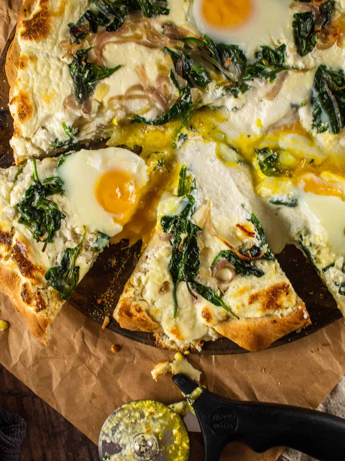breakfast pizza with eggs and spinach that has been sliced
