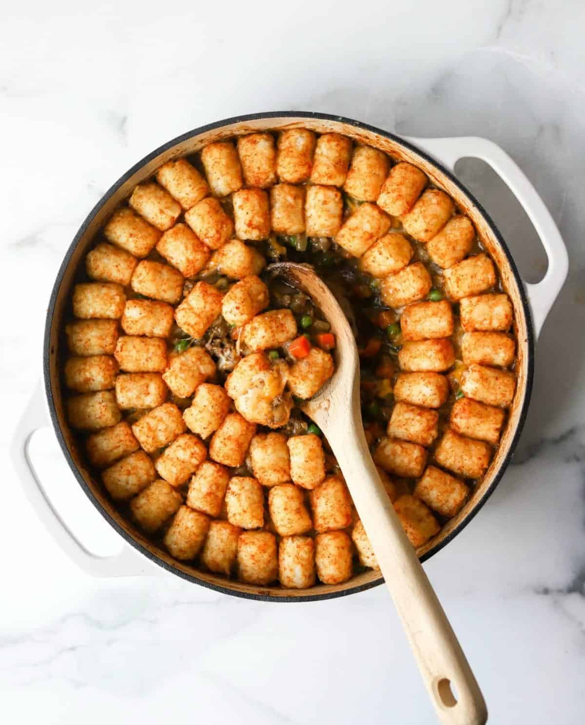 wooden spoon scooping a helping of tater tot casserole