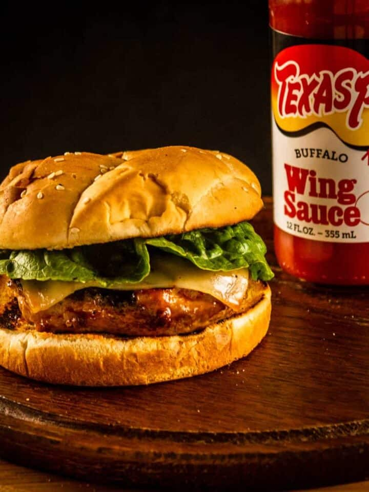 burger on a wooden tray next to a bottle of wing sauce