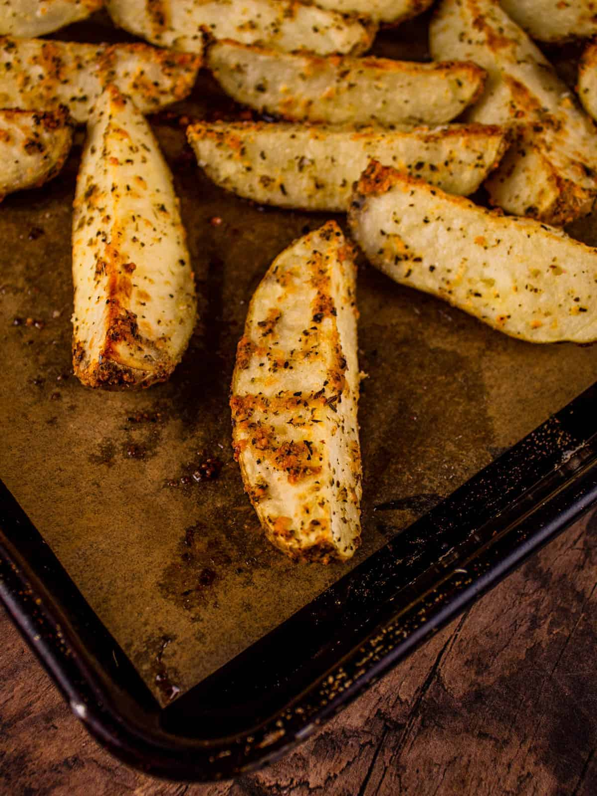 roasted parmesan potato wedges on a sheet pan