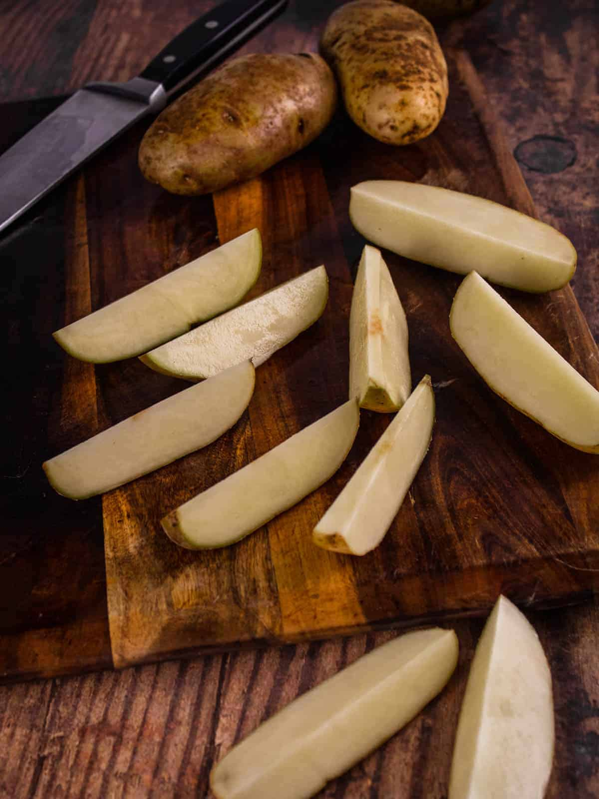 potatoes cut in wedges on a cutting board