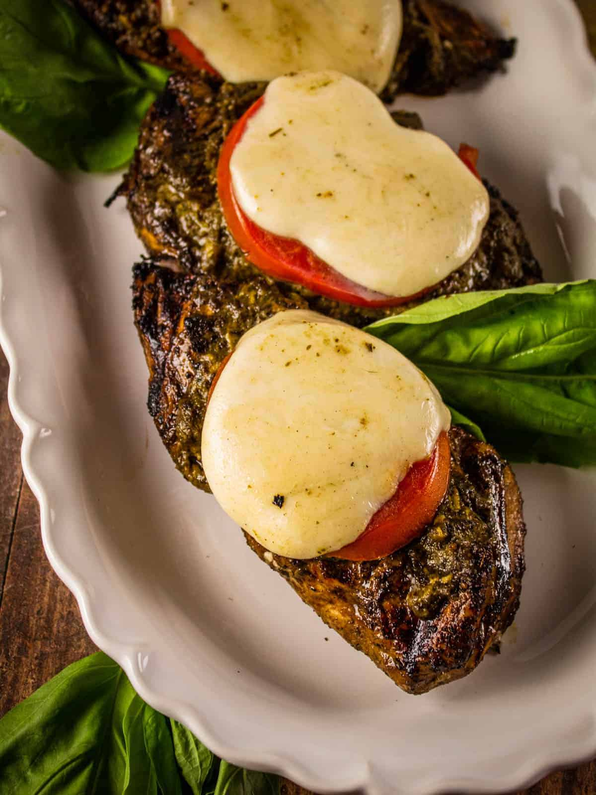 grilled chicken on a white plate topped with pesto, tomato and mozzarella cheese