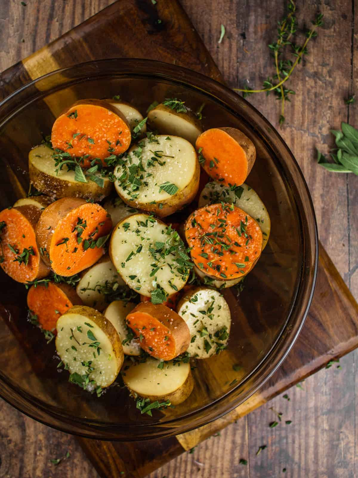 sliced sweet and white potatoes in a glass bowl with fresh herbs