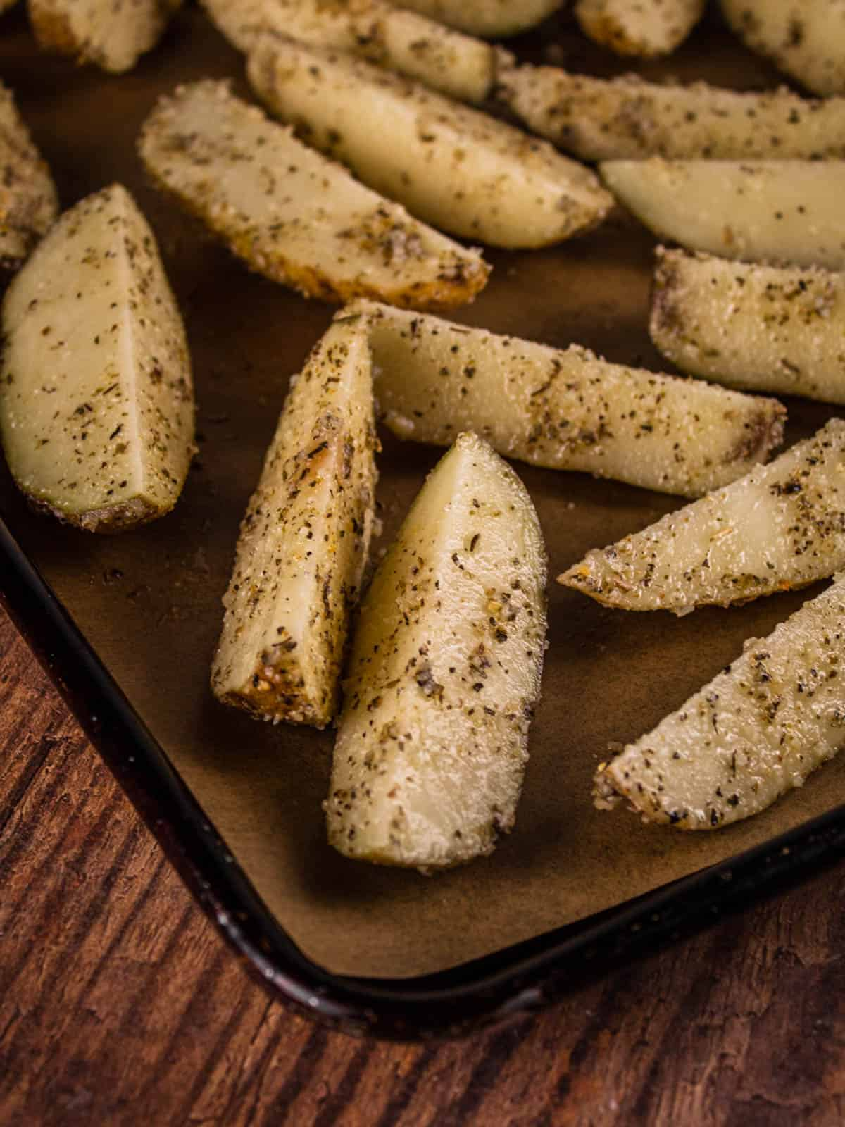 seasoned potato wedges on a sheet pan before baking