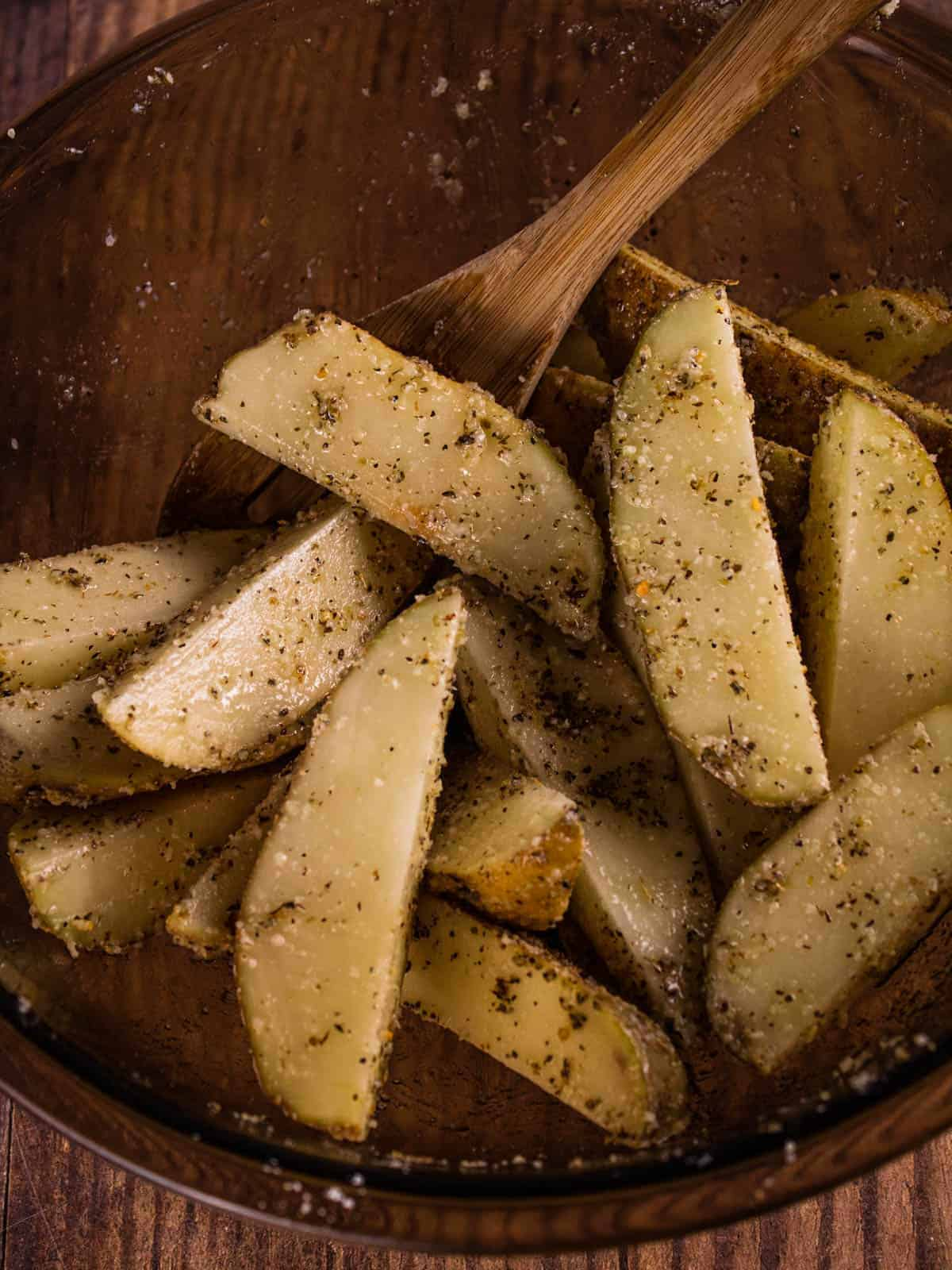 seasoned potato wedges in a mixing bowl
