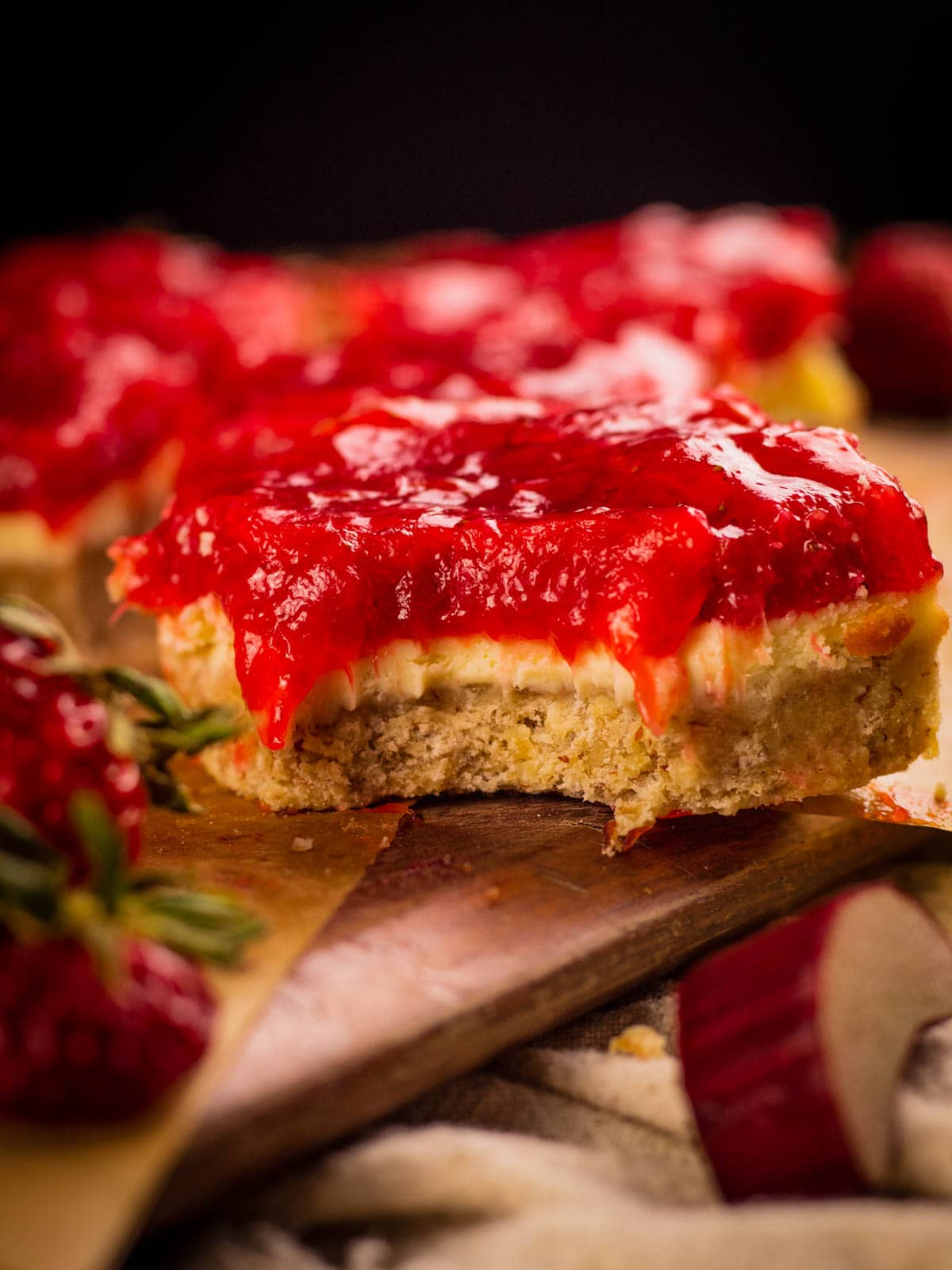 cheesecake bar with red jam on top with a bite taken from it