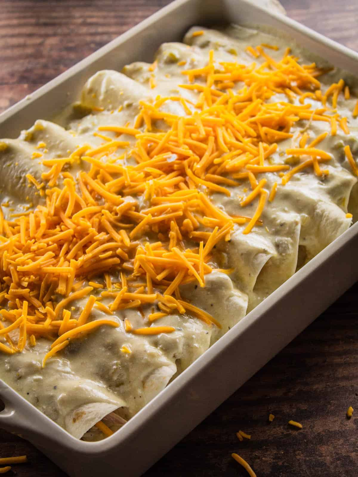 enchiladas topped with sauce and cheese before baking