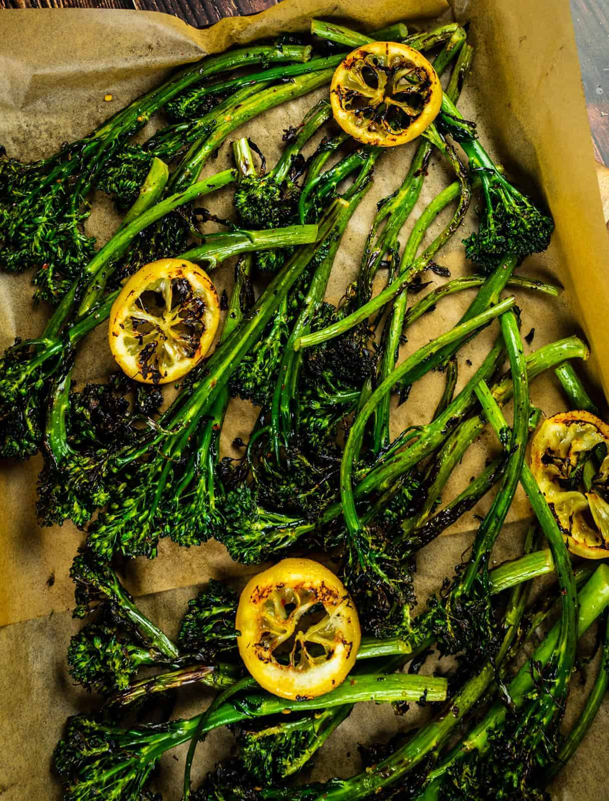 grilled broccolini and lemon slices on parchment paper