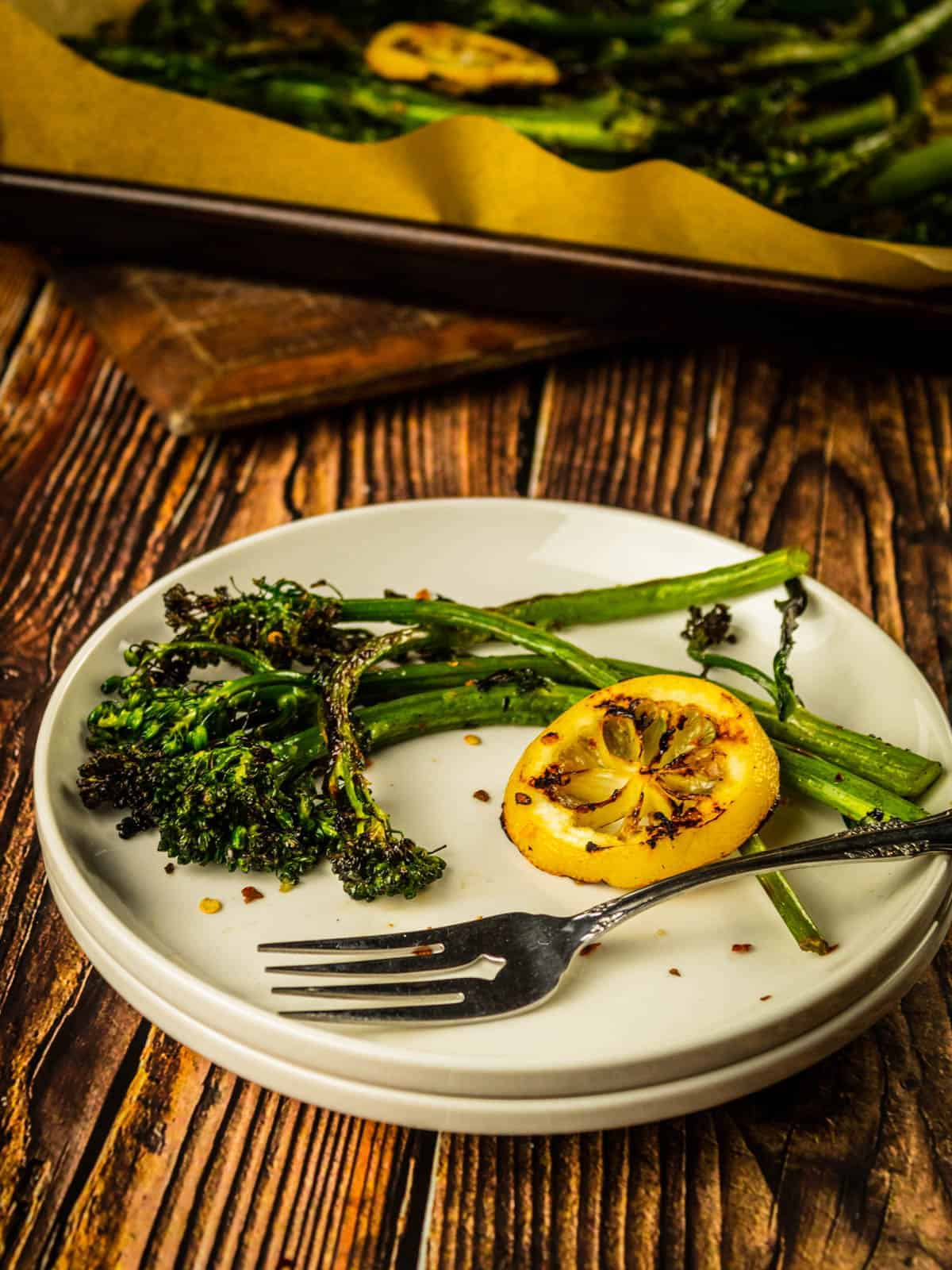 white plate with grilled broccolini and grilled lemon