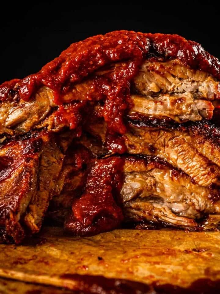 cooked ribs on stacked on top of each other with barbecue sauce dripping down them