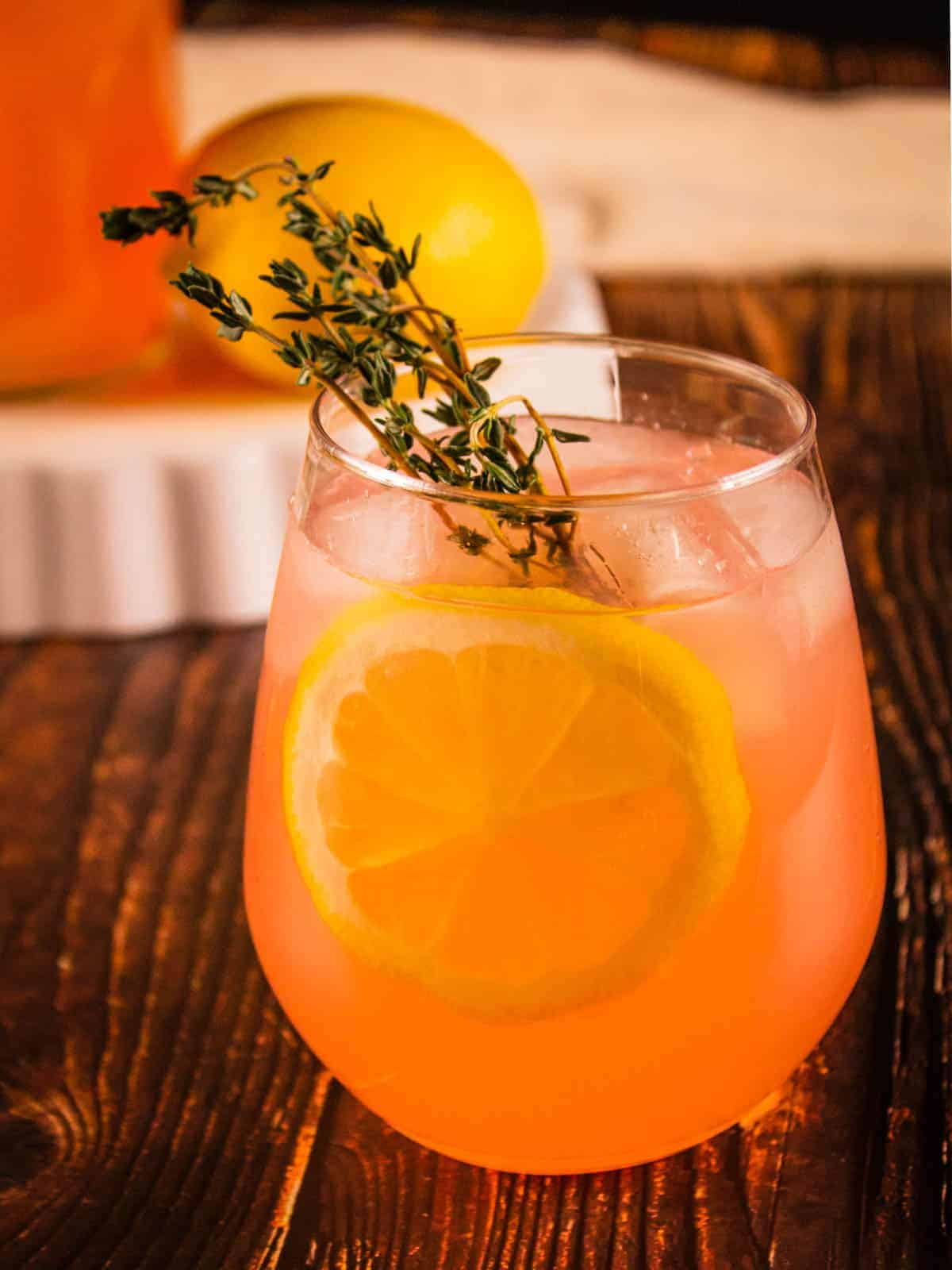 pink lemonade in a stemless wine glass with lemon wheel and fresh thyme sprig