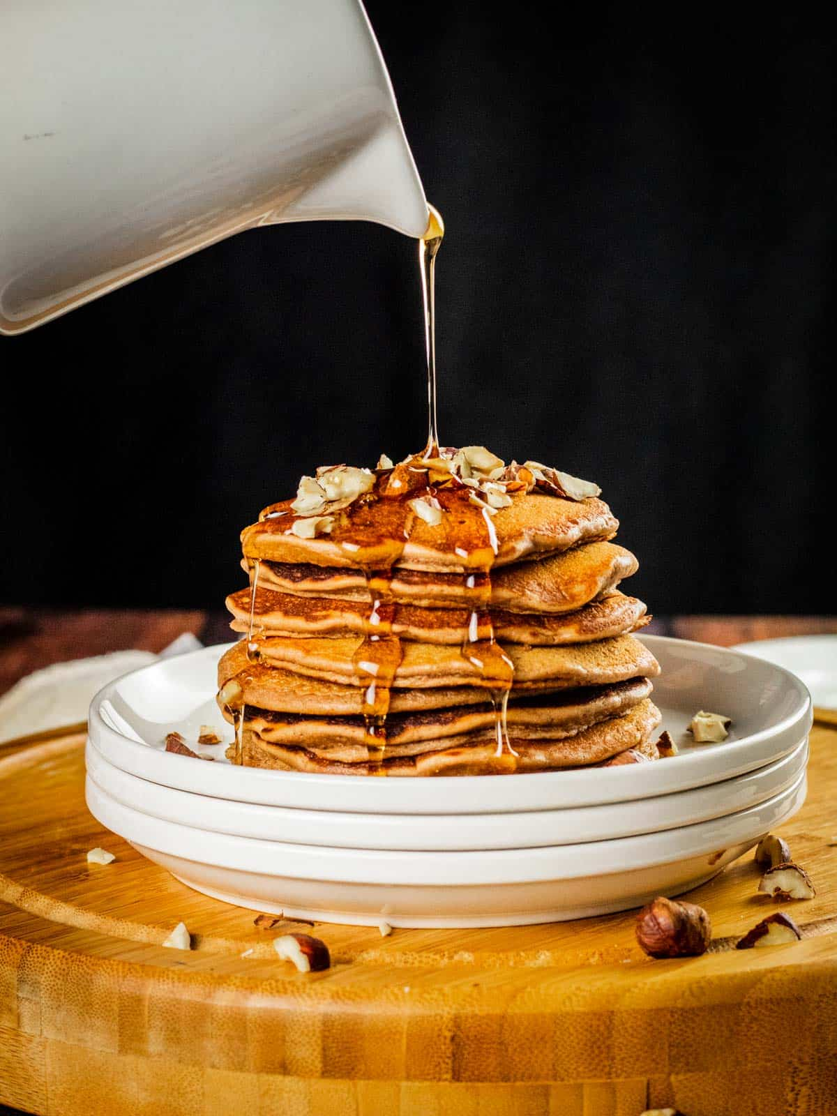 white pitcher pouring syrup over a stack of nutella pancakes on a stack of white plates with chopped hazelnuts