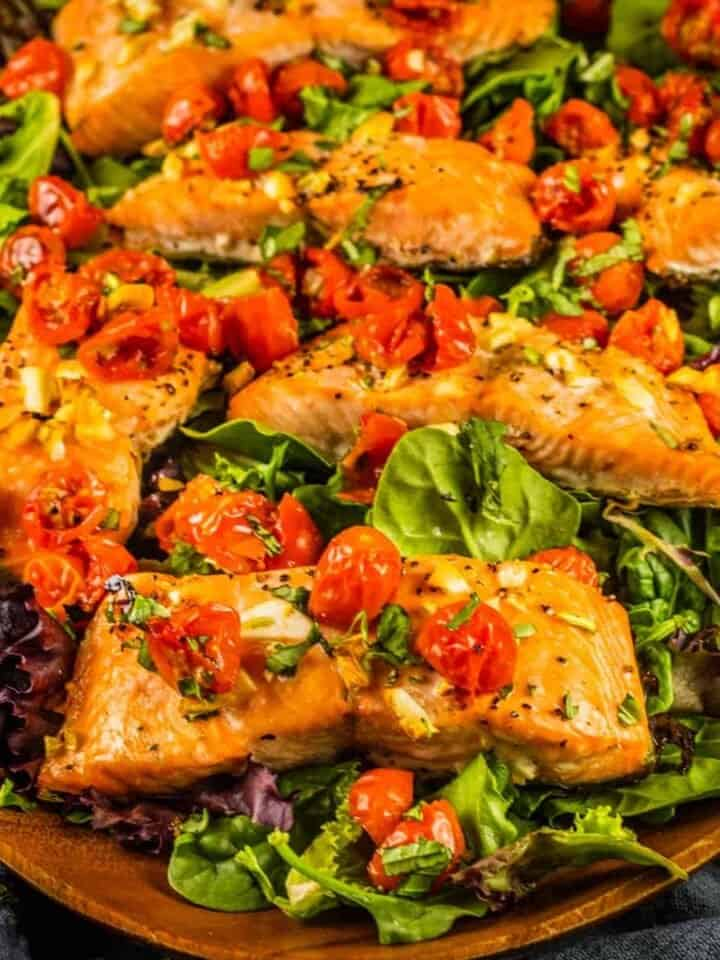 salmon filets on spring salad topped with roasted tomatoes and basil