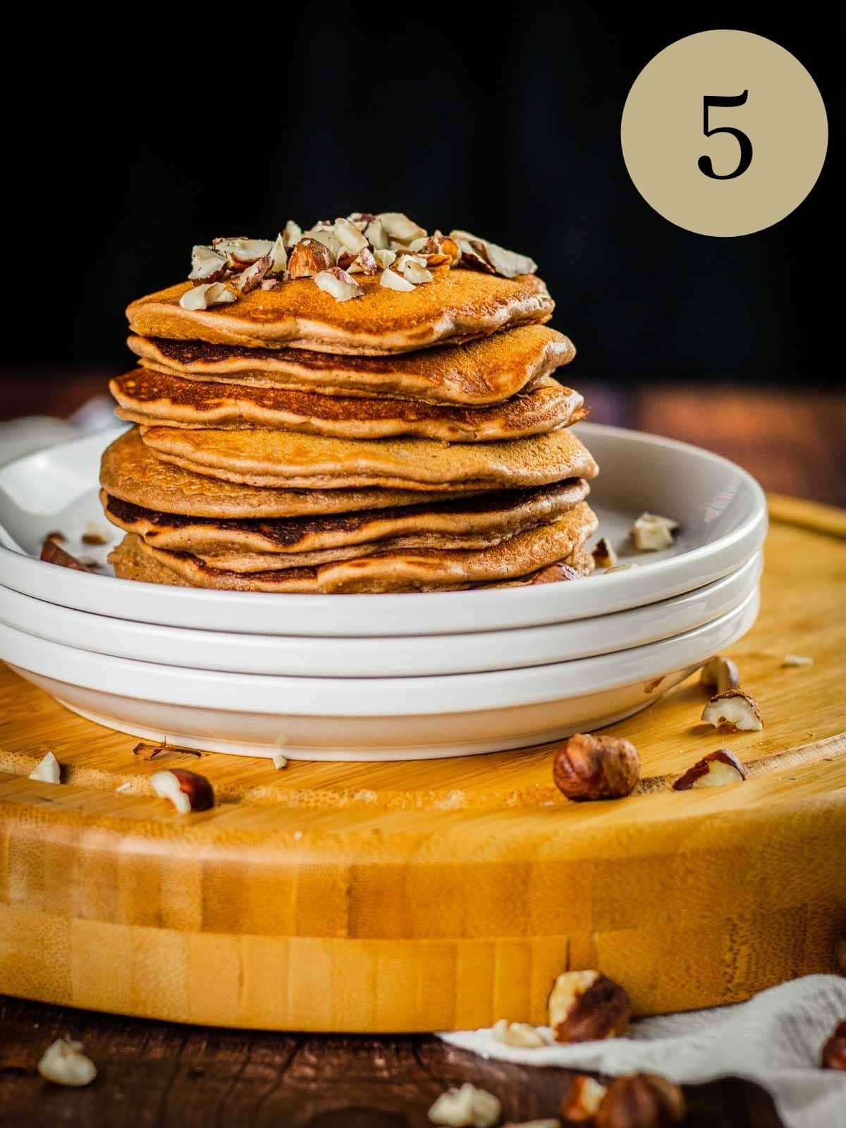stack of nutella pancakes on a stack of white plates topped with chopped hazelnuts