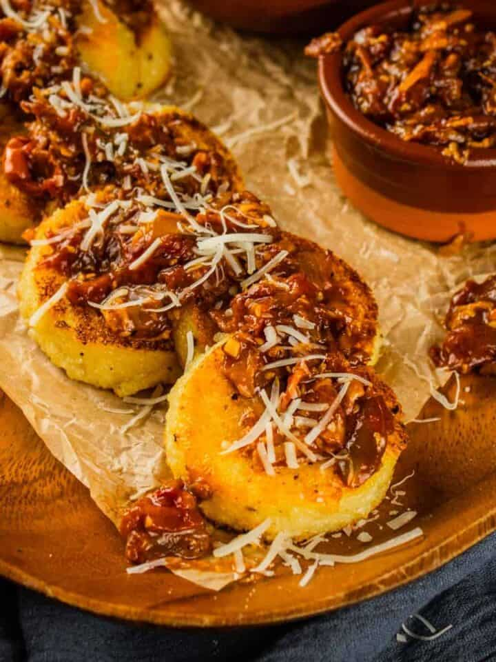 polenta cakes on a wooden tray topped with cheese and tomato bacon jam