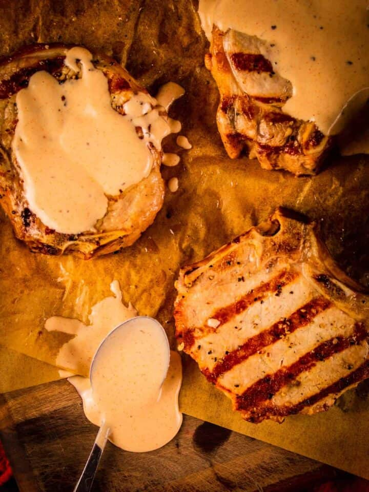 grilled pork chops on a tray covered in white bbq sauce