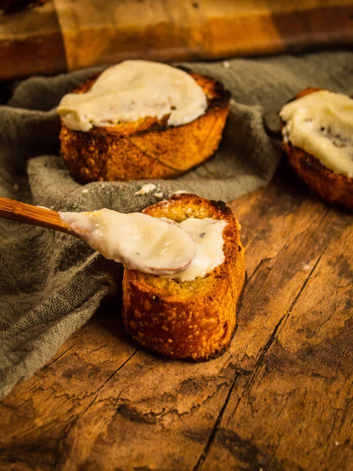 small wooden spoon dropping ricotta spread on baguette slice