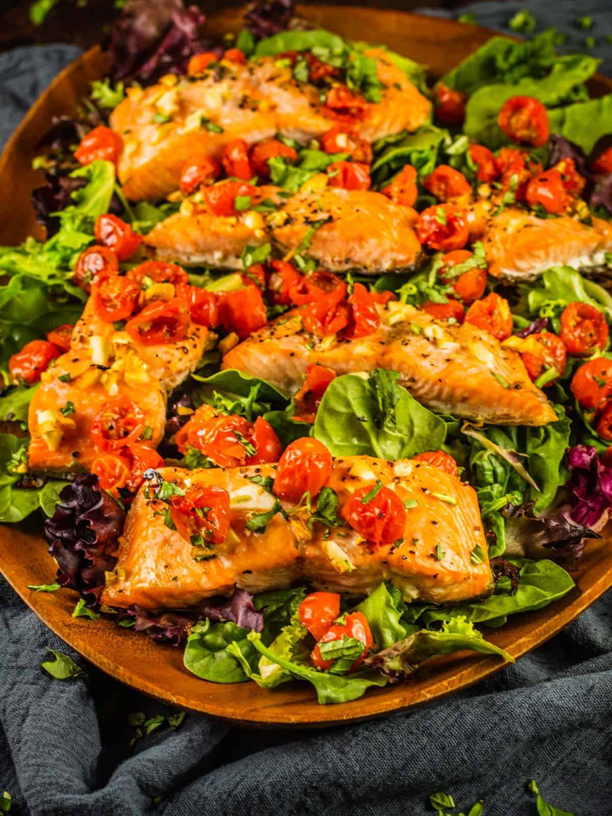 salmon filets topped with roasted tomatoes on top of salad