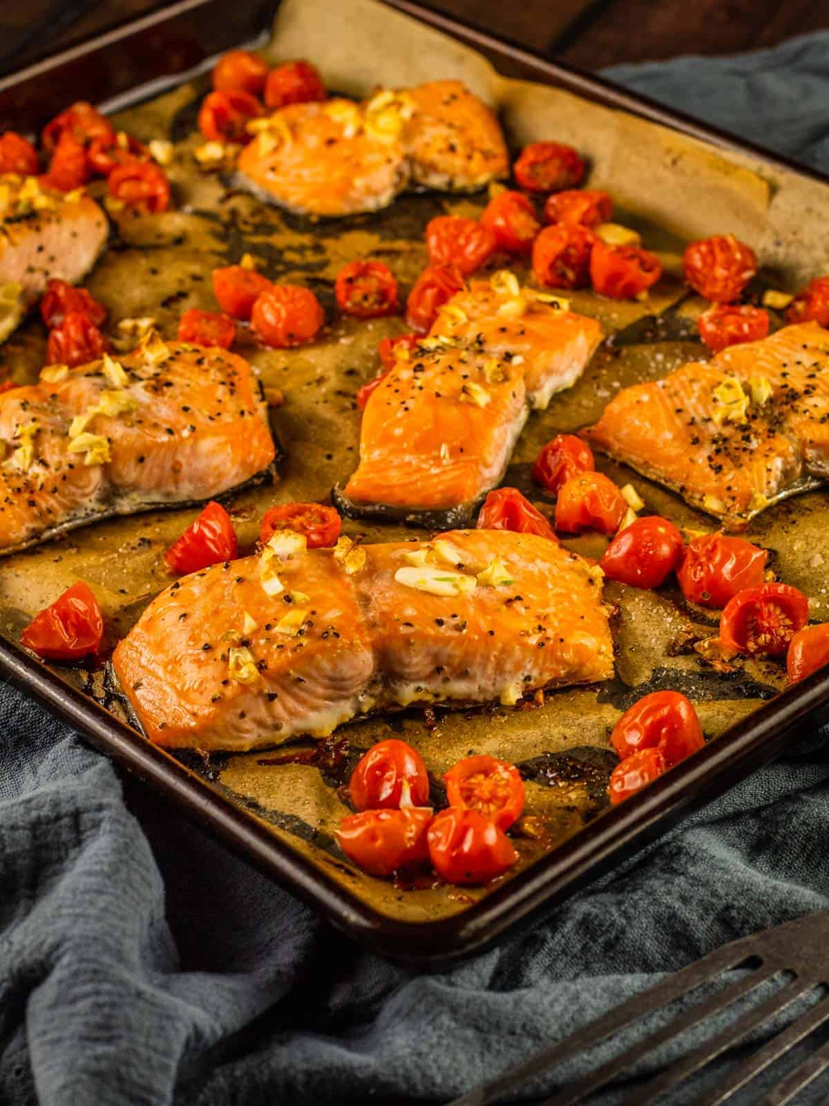 roasted salmon and tomatoes on a sheet pan