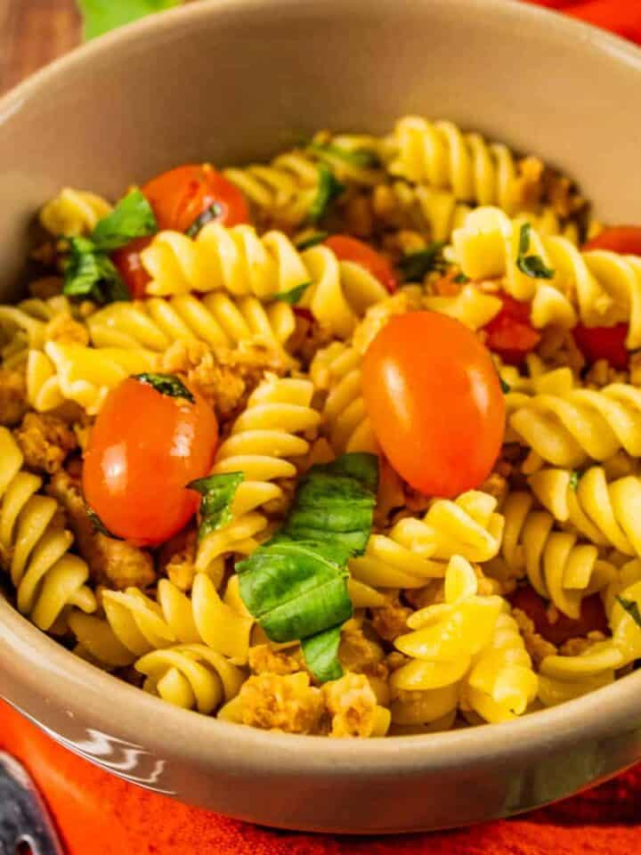 bowl of pasta with sausage, tomatoes and fresh basil