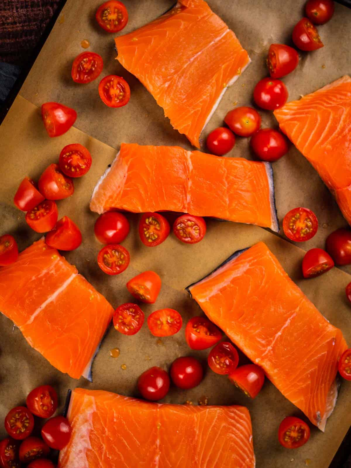 raw salmon filets on a sheet pan with halved tomatoes