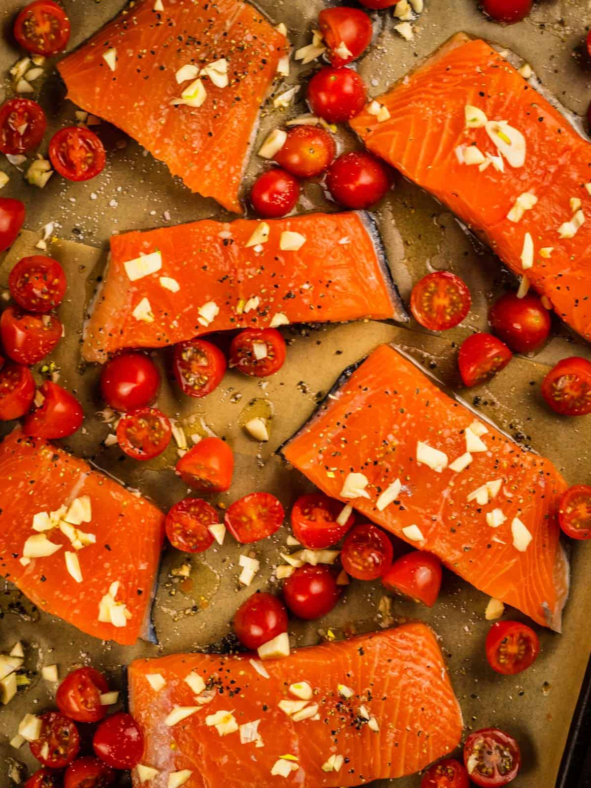 minced garlic on raw salmon filets and halved tomatoes