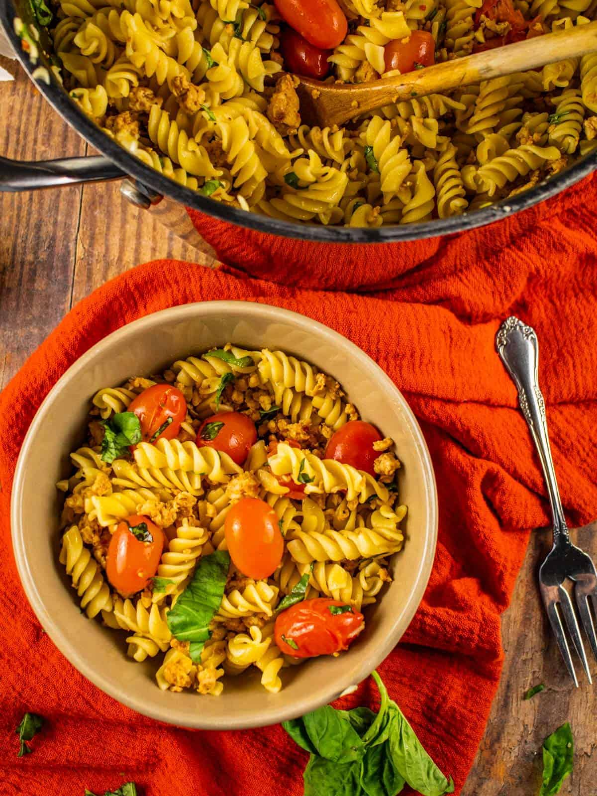 tan bowl and silver pot filled with pasta with tomatoes, basil and sausage