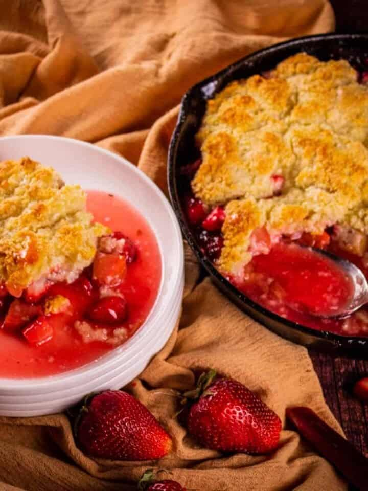 skillet with strawberry rhubarb cobbler and a serving on a white plate