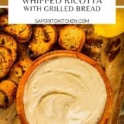 whipped ricotta in a wooden bowl with grilled sliced bread