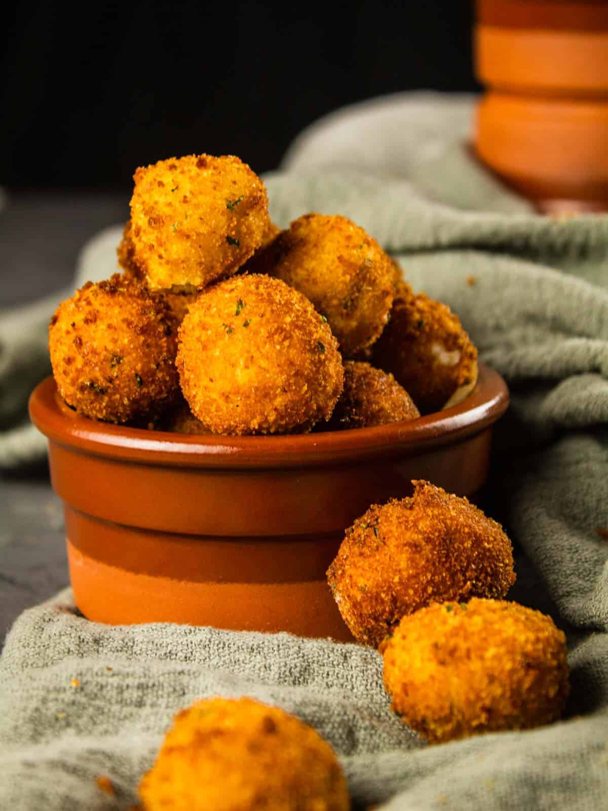 fried goat cheese balls in a terracotta container