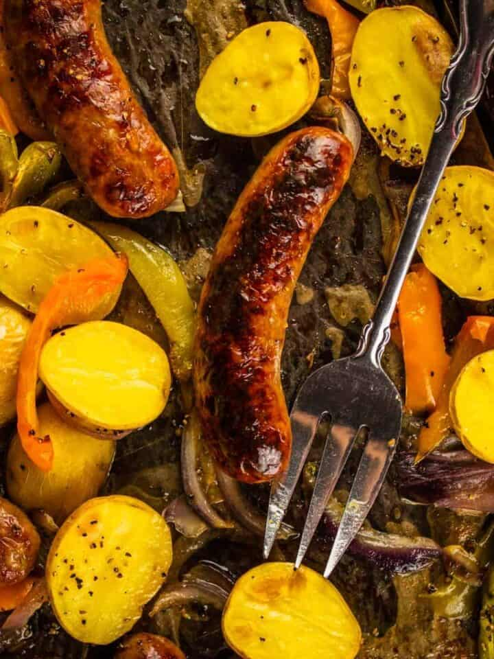 browned sausage on a sheet pan with halved potatoes and sliced peppers and onions