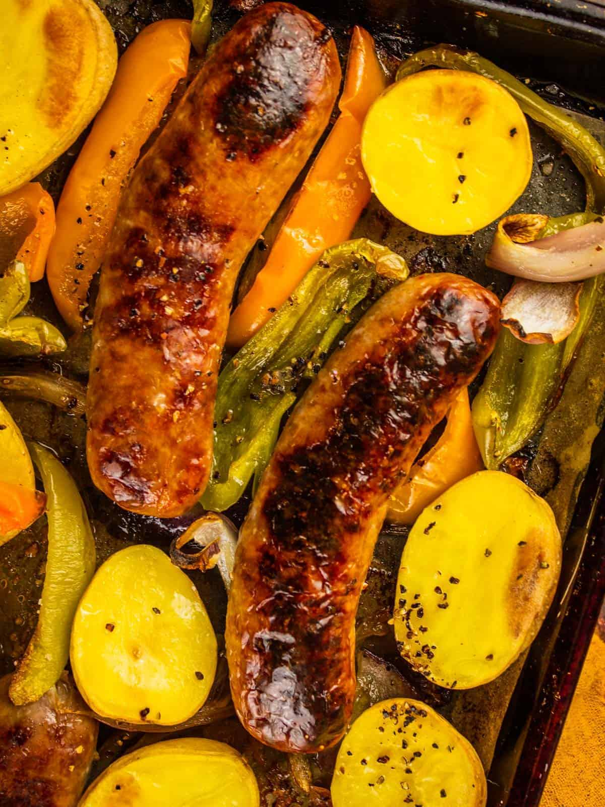 roasted sausages, halved potatoes and slices peppers on a sheet pan