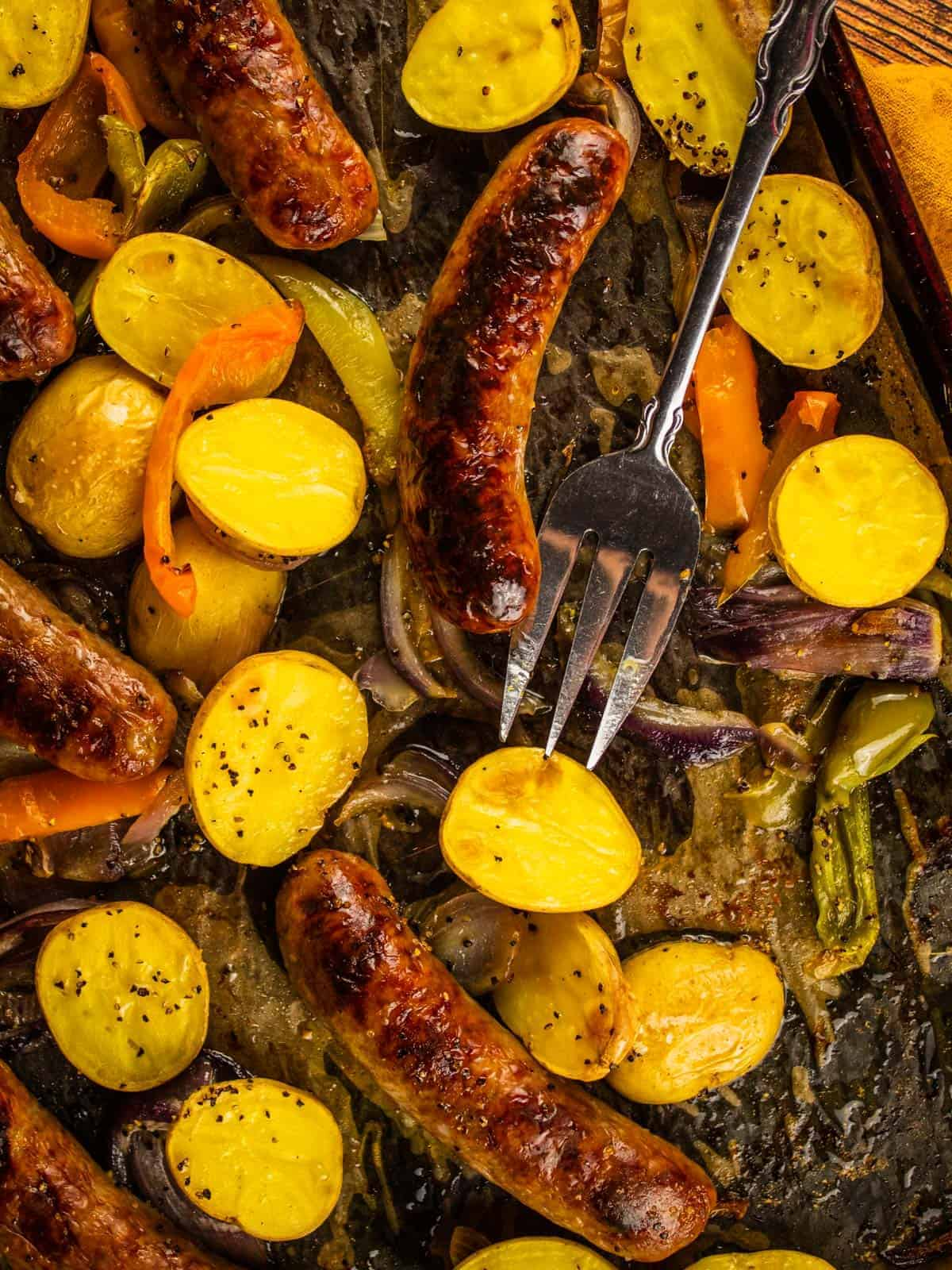 browned sausages on a sheet pan with potatoes, peppers and onions and a serving fork