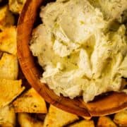 creamy dip in a wooden bowl surrounded by bagel chips