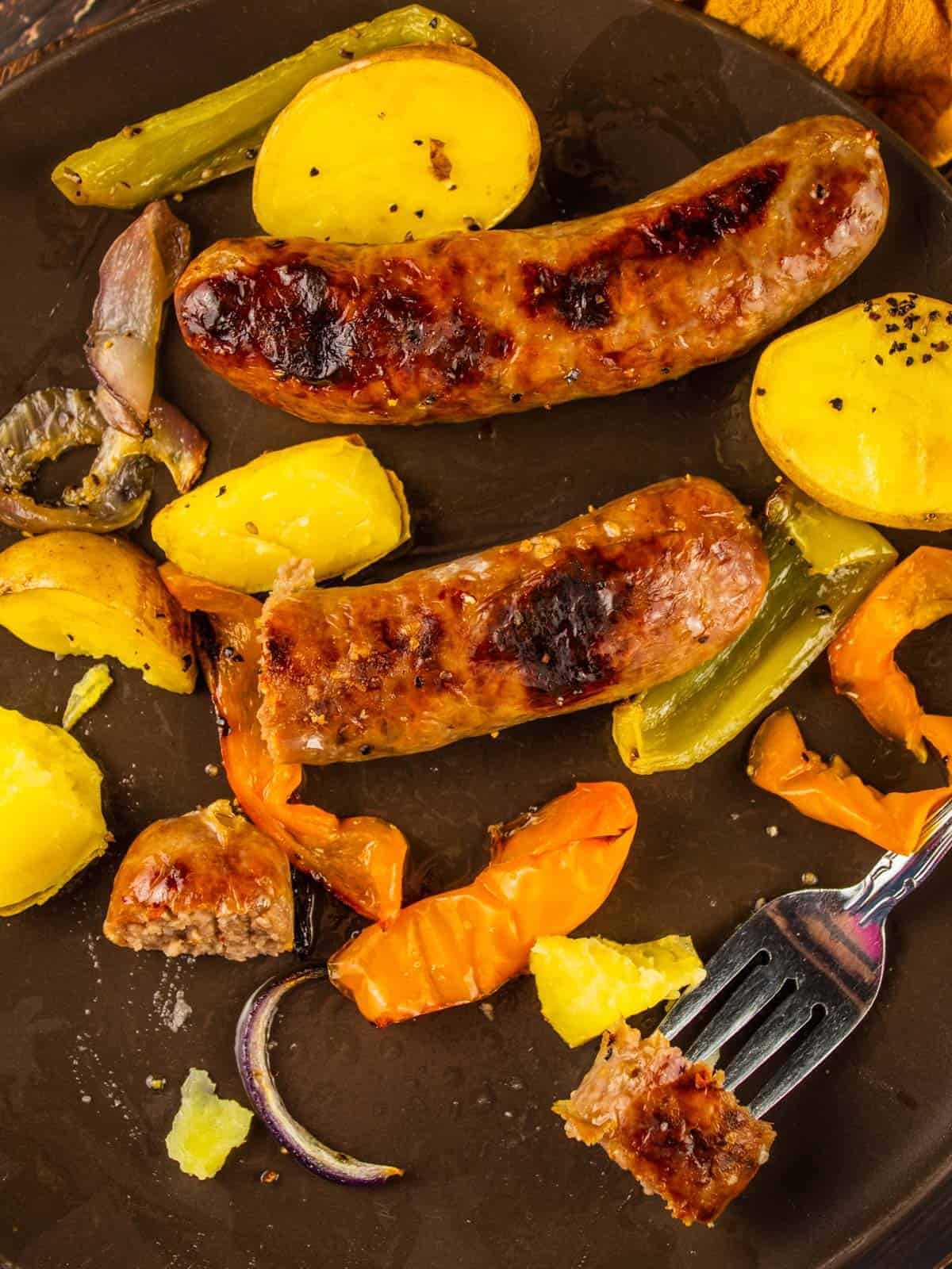 roasted sausages, potatoes and peppers on a brown plate with a fork