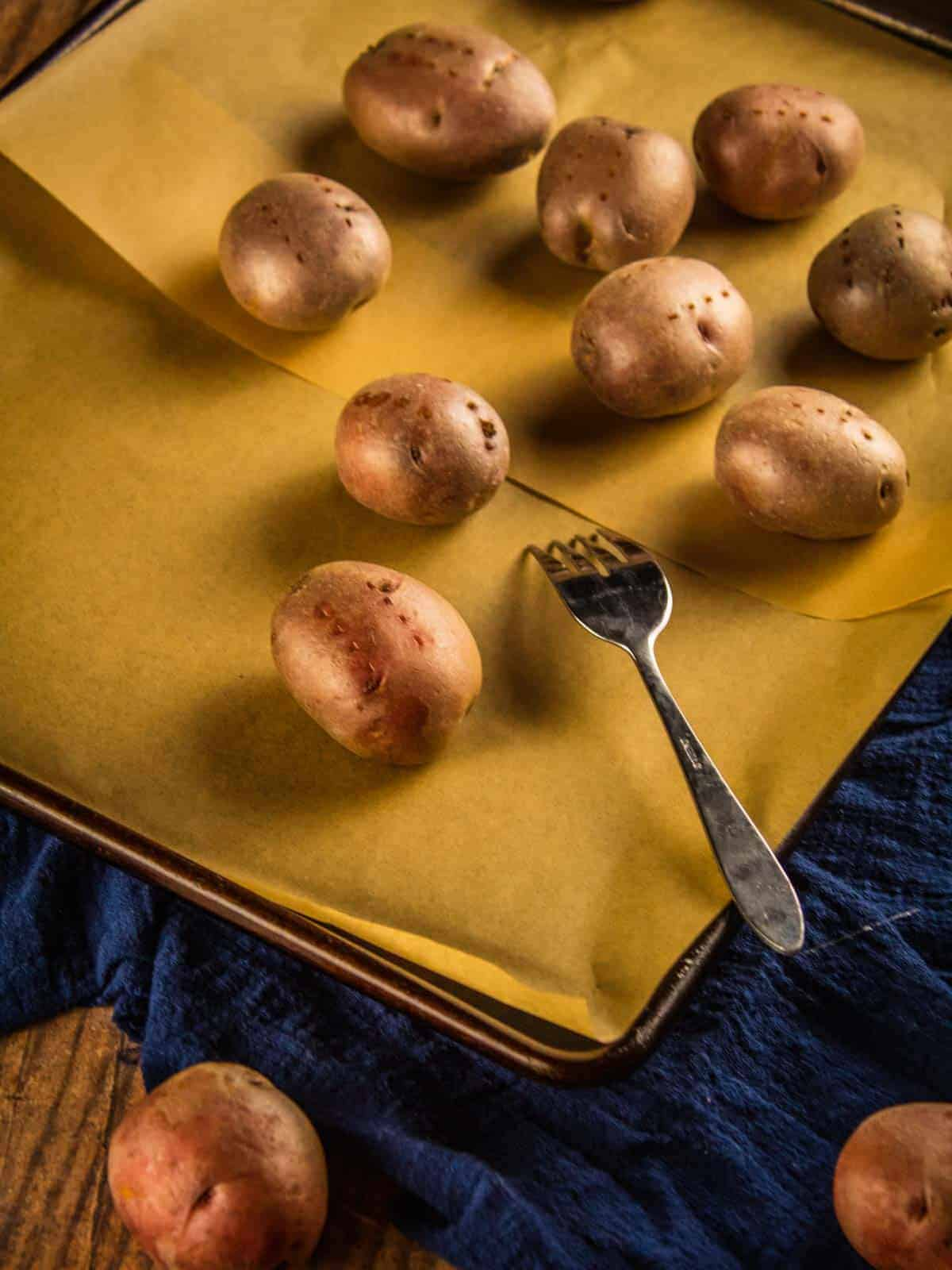 red potatoes that on a sheet pan with a fork