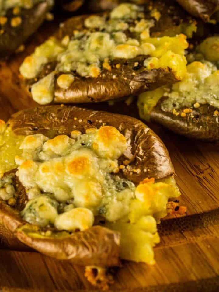 smashed red potato topped with browned blue cheese crumbles on a wooden tray