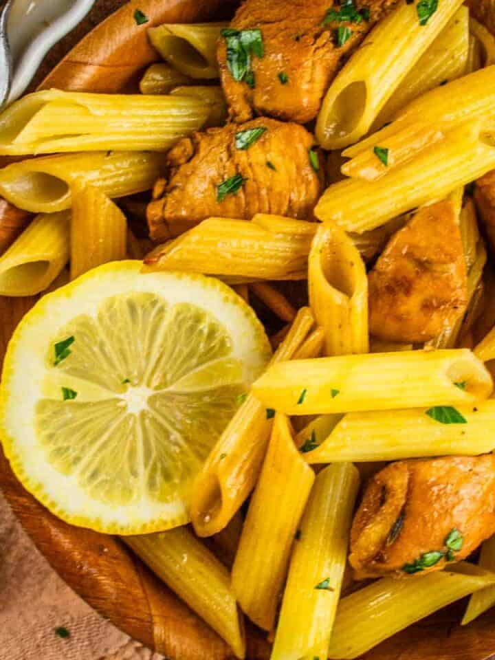 penne pasta in a wooden bowl with chicken, fresh parsley a fork and lemon slices