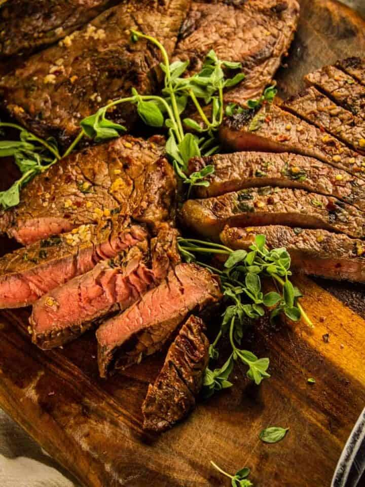 cutting board with partially sliced grilled sirloin steak and fresh oregano stems and knife