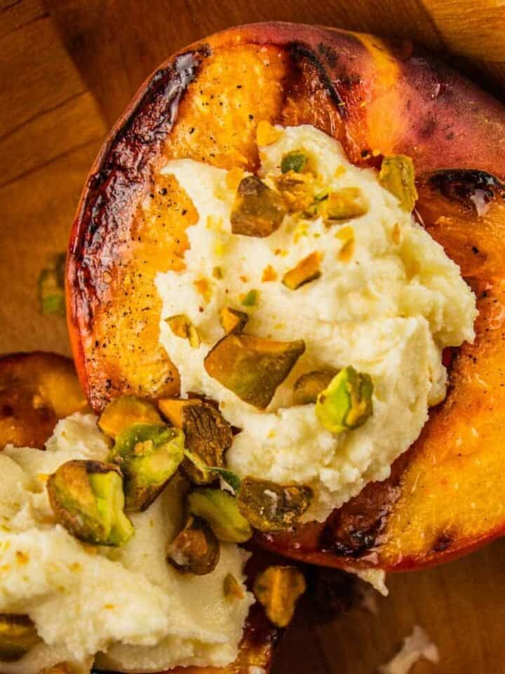 grilled peach halves topped with honey mascarpone and pistachios in a wooden bowl