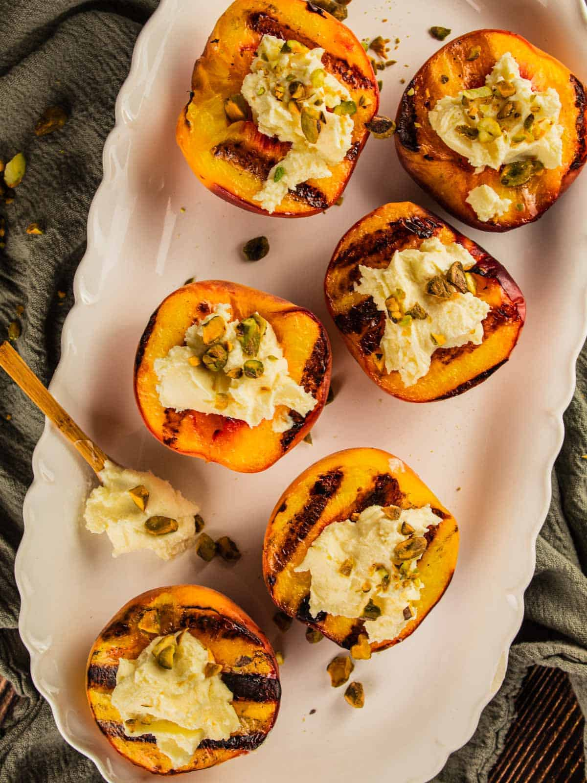 grilled peaches topped with mascarpone and pistachios on a white platter