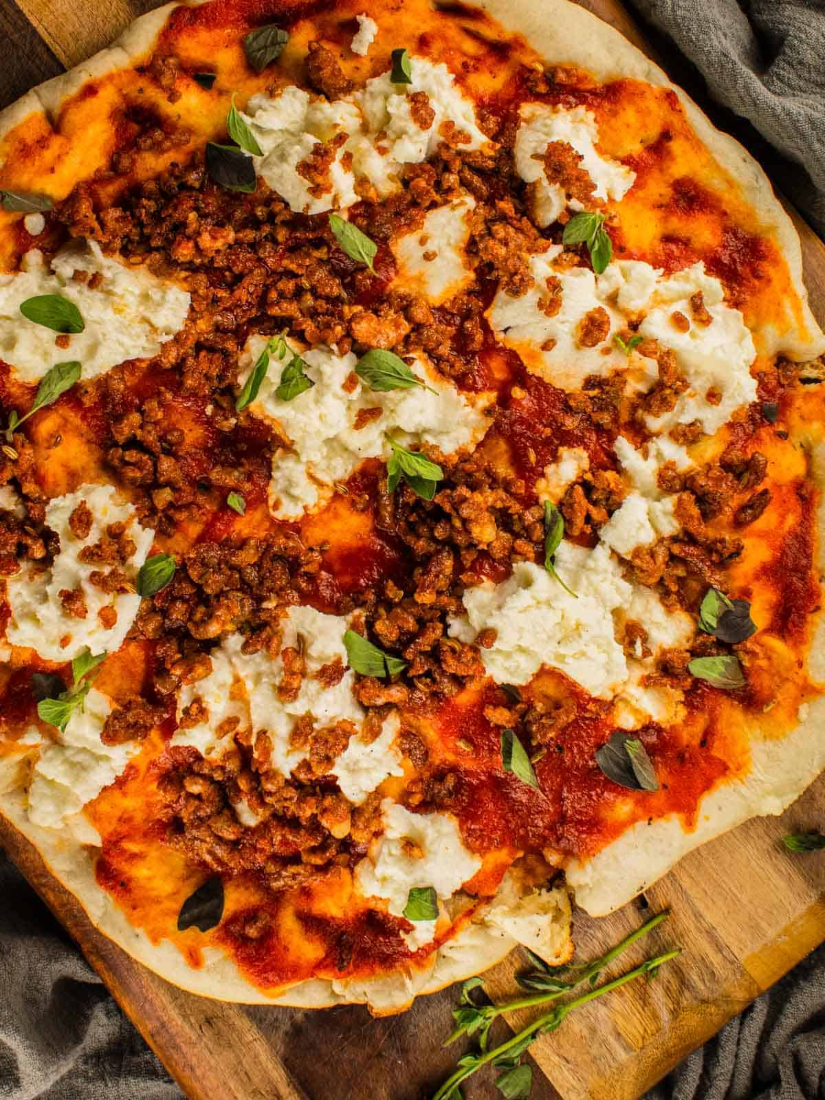 grilled pizza with marinara, ricotta, sausage and oregano on a cutting board