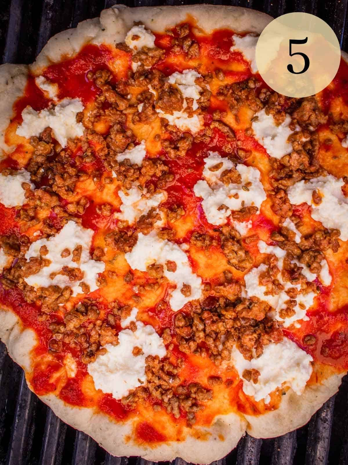 pizza cooking on a grill with marinara, sausage and ricotta