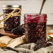 two mason jars filled with homemade blackberry jam with fresh blackberries around it