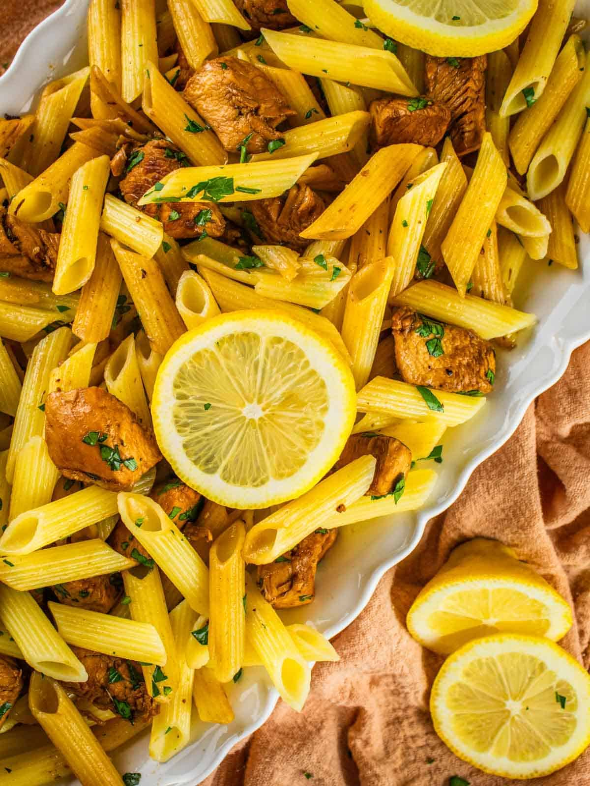 white platter of penne pasta with chunks of chicken, slices of lemon and fresh parsley