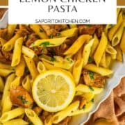 penne pasta with lemon chicken, fresh parsley and lemon slices on a white platter