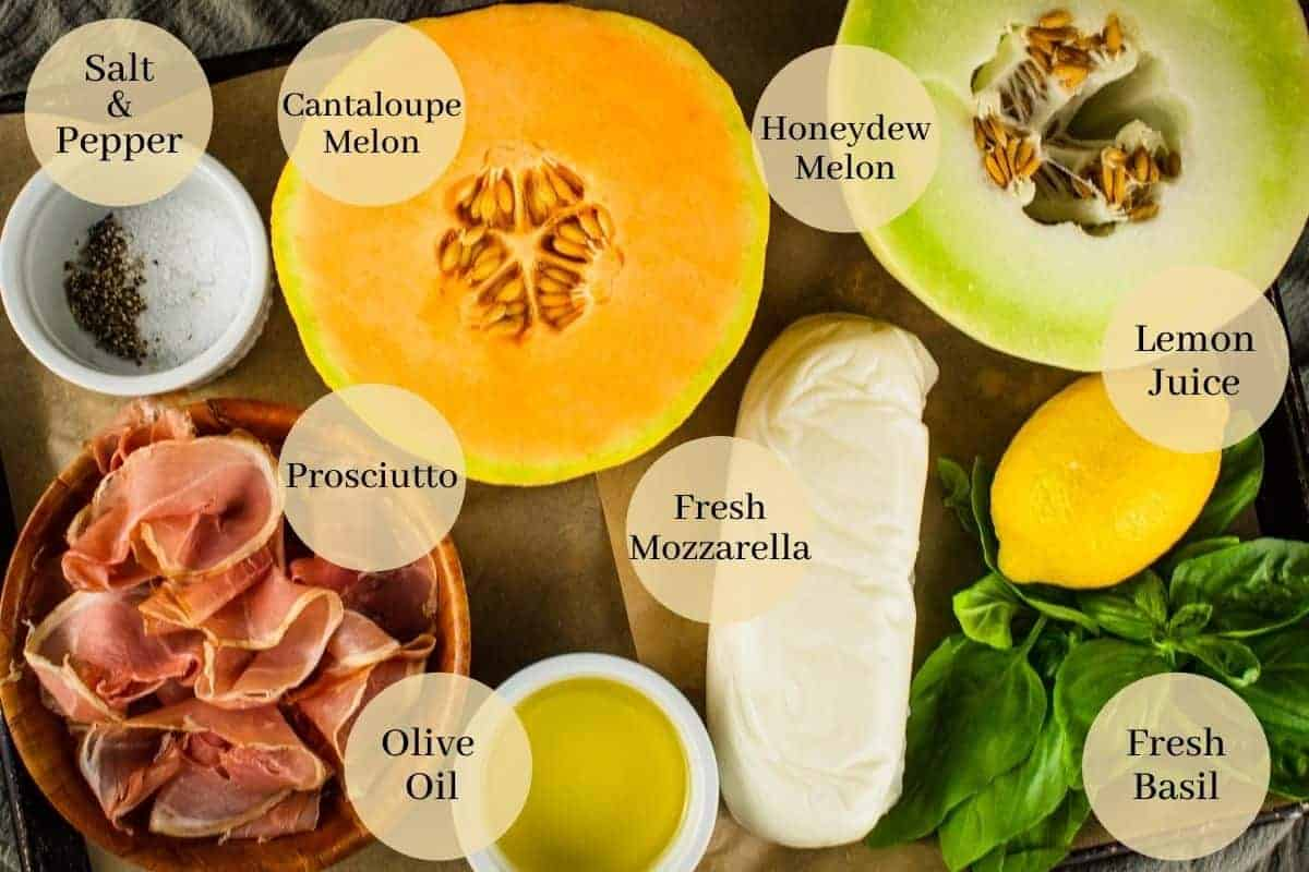 honeydew, cantaloupe, prosciutto, mozzarella, lemon, basil leaves, olive oil and salt and pepper on a tray
