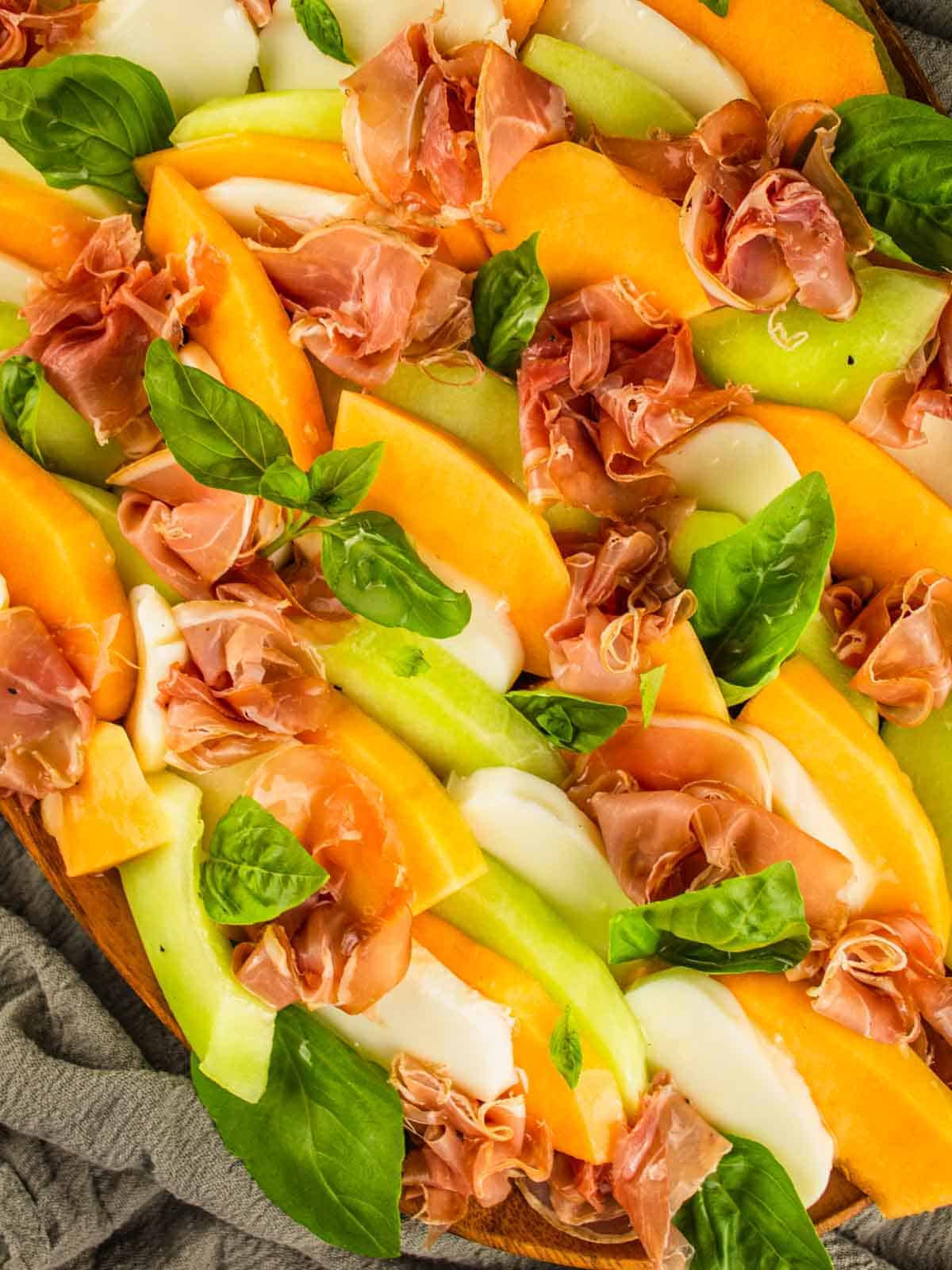 slices of honeydew, cantaloupe and mozzarella layered with thinly sliced prosciutto and fresh basil leaves