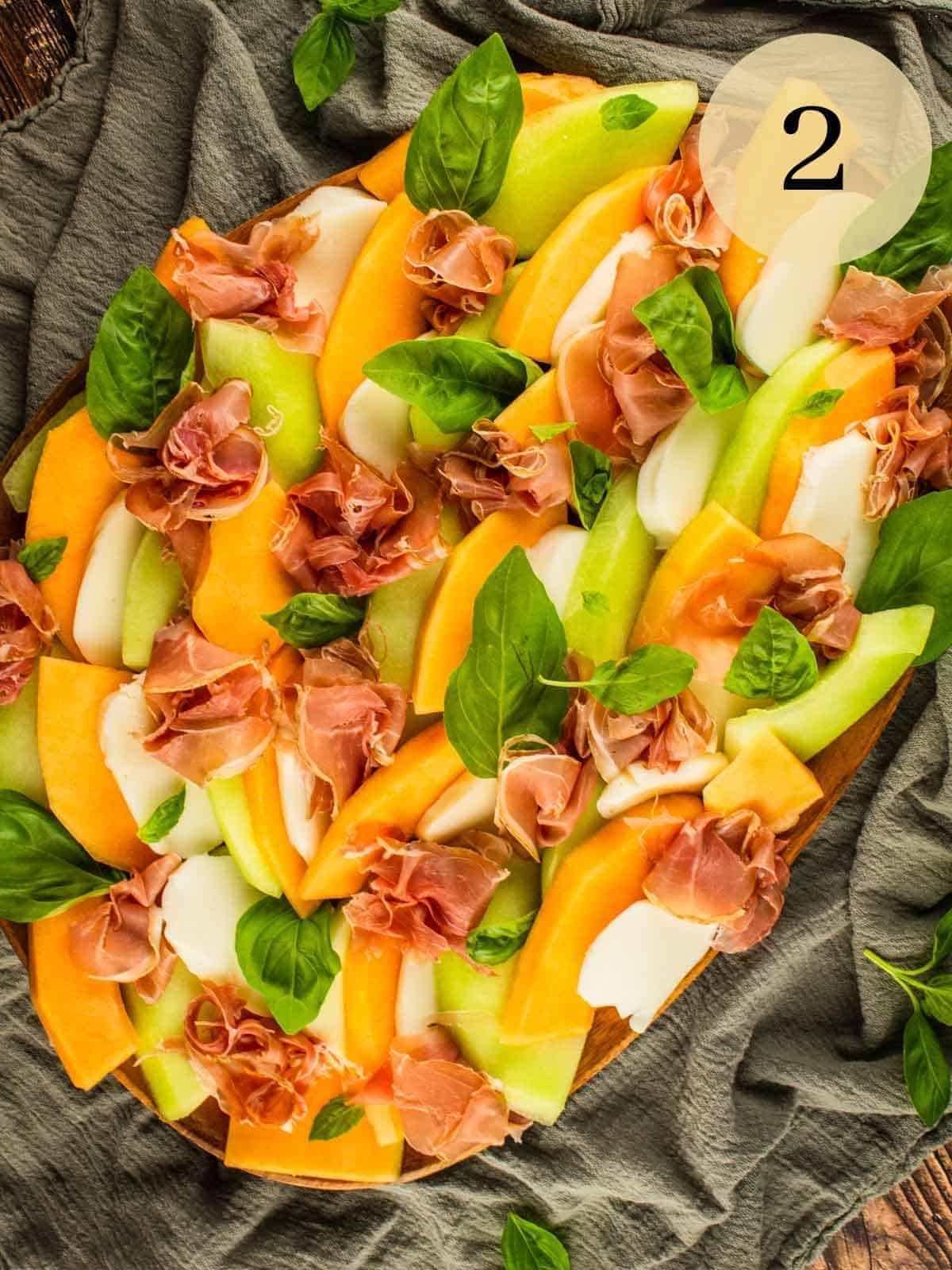 honeydew, cantaloupe and mozzarella layered on a tray with prosciutto and fresh basil leaves