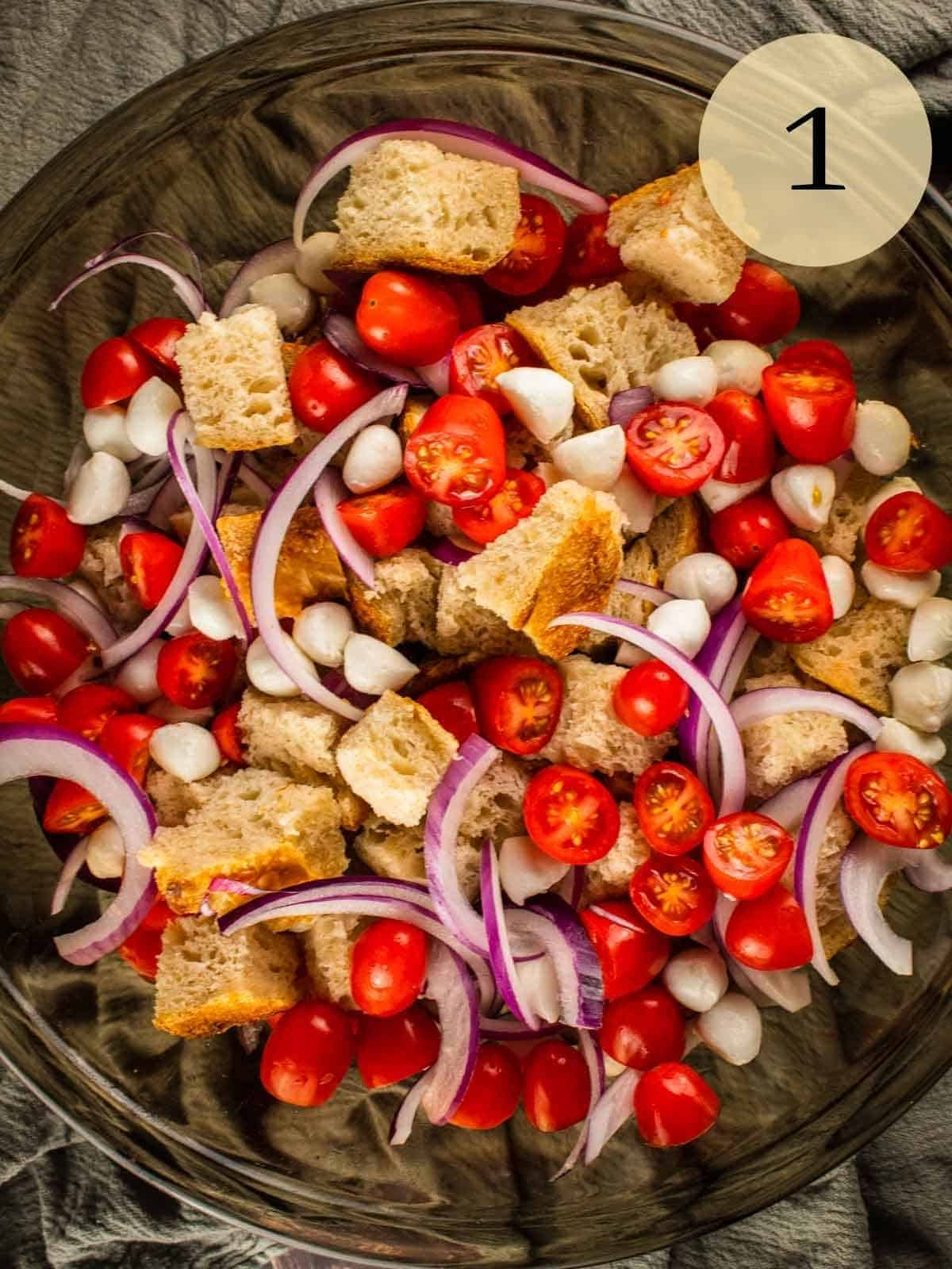 bowl with cubes of bread, sliced red onion, halved grape tomatoes and mozzarella balls